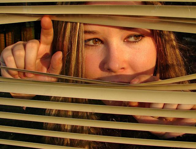 Lady peeking through some blinds
